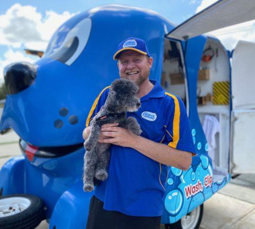 dog grooming uniform, grooming salon, mobile grooming salon, blue dog, dog trailer, mobile dog grooming salon, male groomer, male dog groomer, dog groomer, mobile dog wash trailer, Blue Wheelers trailer