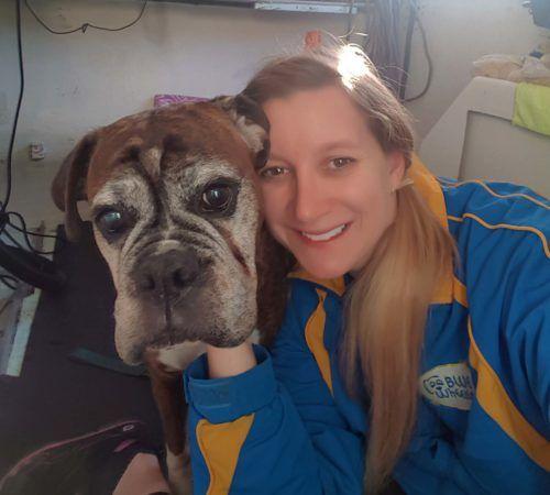 Lady holding dog, cute dog, woman holding dog, blue wheelers logo, dog grooming uniform, lady dog groomer, cute dogs, female groomer, female dog groomer, dog, dogs, cute puppy, pup, dog love, doggie love