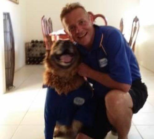 dog grooming uniform, male groomer, dog groomer, mobile dog groomer, mobile dog wash trailer, golden retriever, dog wearing uniform, cute dog, dog with a groomer