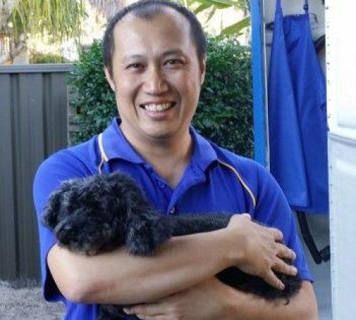 man holding dog, cute dog, groomer holding dog, blue wheelers logo, dog grooming uniform, male groomer, male dog groomer, dog groomer,